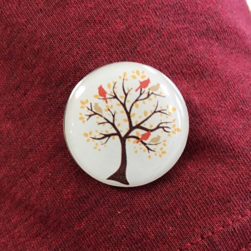 Cardinal Living pin with tree and branches, leaves, and birds in the tree.