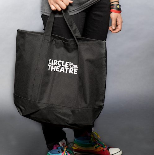 Black circle theatre tote held by woman wearing rainbow painted Converse.