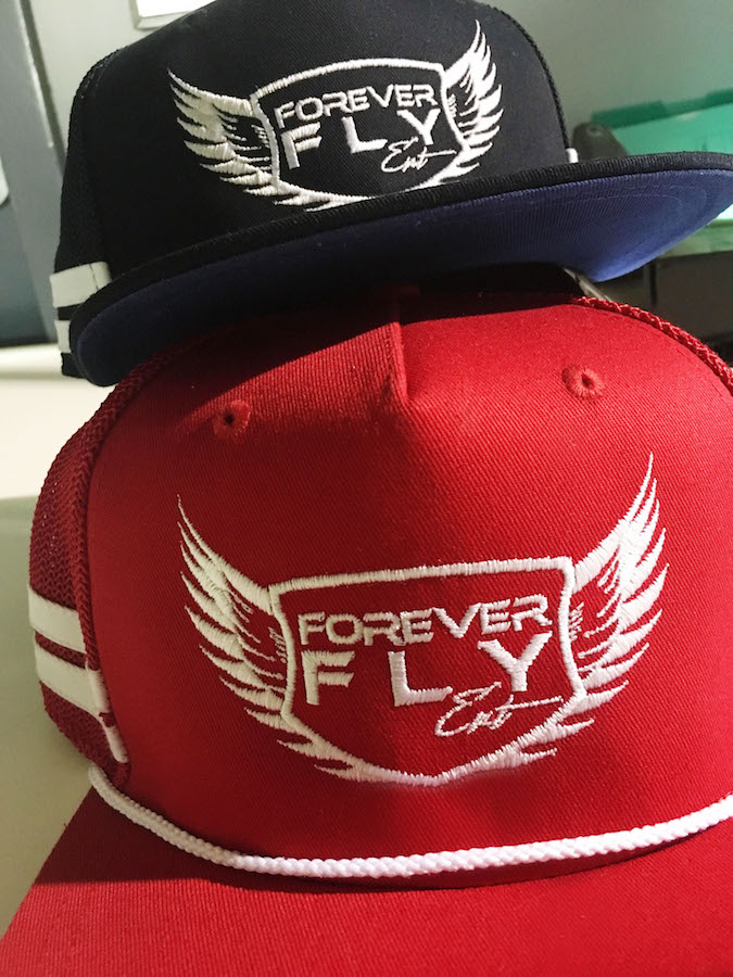 Forever Fly embroidery on navy and red hats, featured on MarkIt Merchandise's blog.
