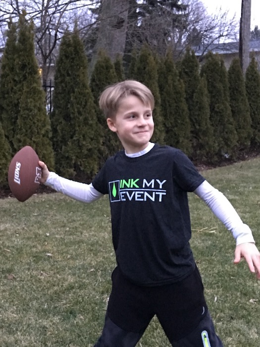 Boy throwing football and modeling charcoal gray Ink My Event t-shirt