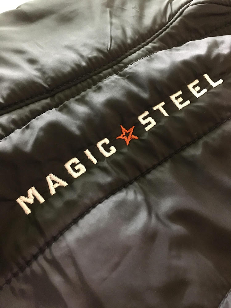 Magic Steel Embroidery close up on black vest, featured on MarkIt Merchandise's blog.