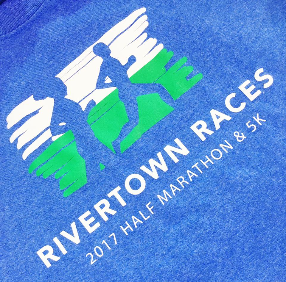 Promotional Rivertown Races on blue t-shirt with green and white logo